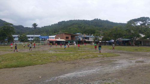 Enfants jouant au foot sur un terrain vague