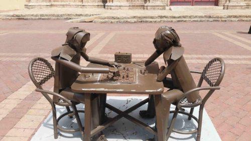 Statue en métal de deux personnes jouant aux échecs