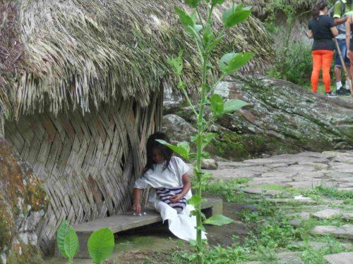 Fillette qui joue au billes devant une hutte