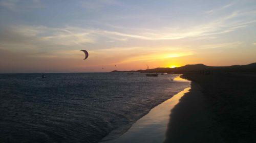 Un kitesurf volant devant un coucher de soleil