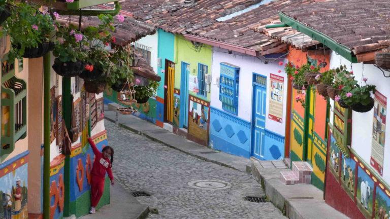 Jeune fille dans une ruelle pavée aux façades décorées