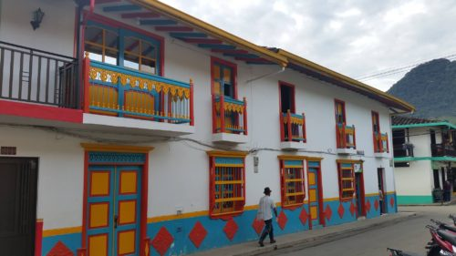 Homme marchant devant une façade très colorée à Jardin