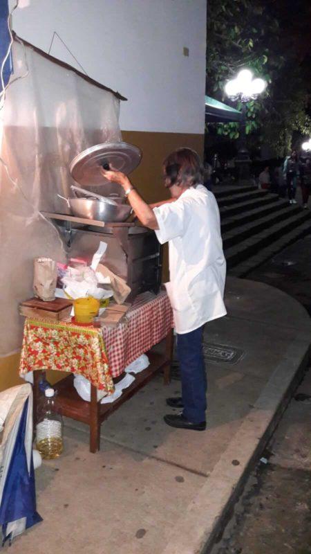 Femme cuisinant dans la rue