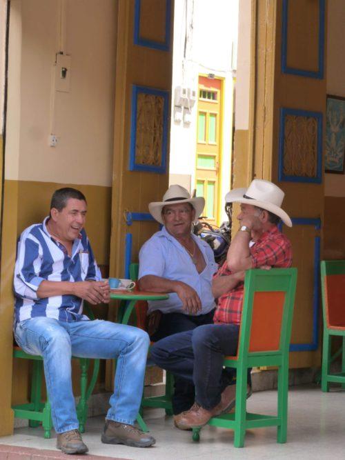 Groupe d'hommes assis dans un café portant des chapeaux blancs