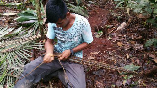Guide construisant un piège à poisson avec du bois et des lianes