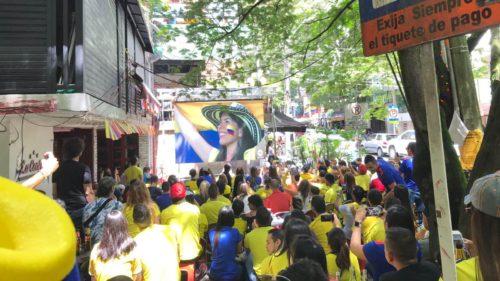 Public vêtu du tshirt de l'éuipe de foot colombienne regardant un écran