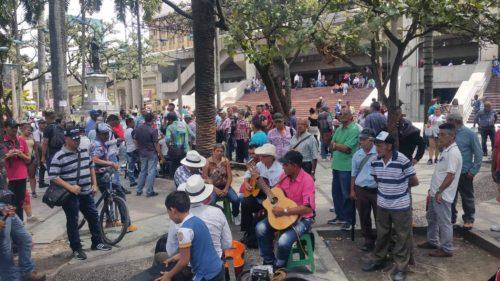 Groupe de personnes écoutant jouer un groupe de musique sur une place