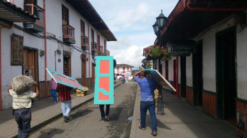 Hommes portant des portes peintes de couleurs vives