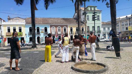 Groupe d'hommes faisant de la capoeira sur une place