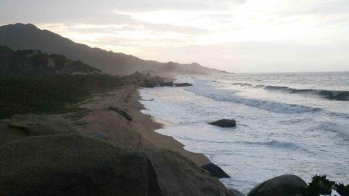 Longue plage avec de l'écume au coucher de soleil